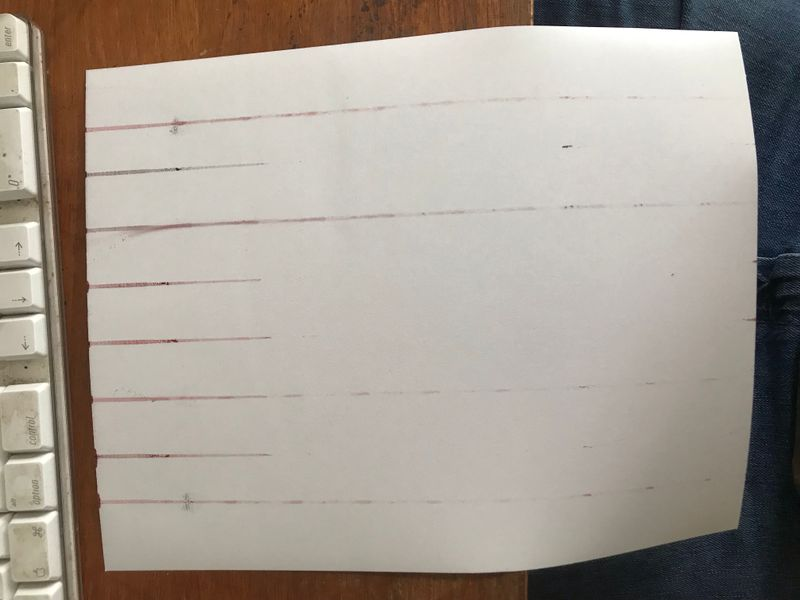The reverse of the paper, showing the ink streaks that are being printed instead of 80% of the design on the correct side.